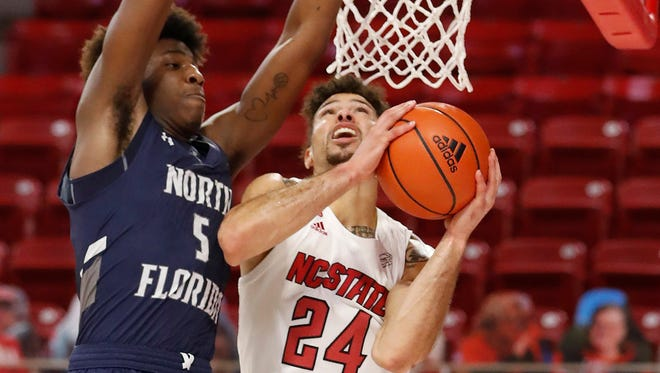 North Florida's Dorian James defends Devon Daniels of N.C. State on Nov. 27 in Raleigh, N.C. The Ospreys return to North Carolina on Saturday to play their fifth road game in a row, and the third in that state.