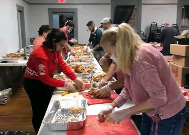 Voluntários preparando centenas de refeições que foram oferecidas a indivíduos carentes pela Sociedade Cultural Açoriana no Dia de Acção de Graças.