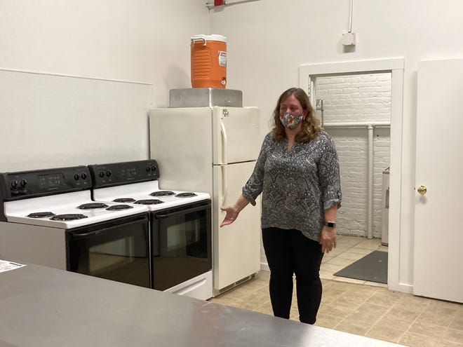 Lisa Mello, wife of Solomon's Porch's Pastor Tom Mello, shows off the new kitchen in the overflow shelter that will provide a hot meal daily for its homeless clients.