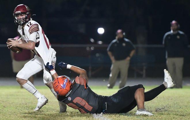 Lake Gibson quarterback Logan Hackett escapes the grasp of a Southeastern defender in last week regional semifinal game.