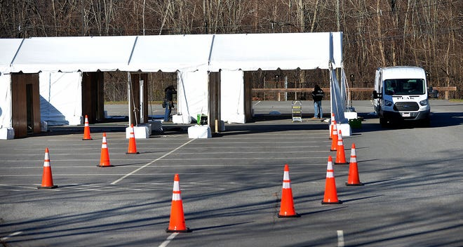 Workers assemble a COVID-19 testing site in a parking lot owned by Framingham State University on Franklin Street on Thursday, Dec. 3, 2020.