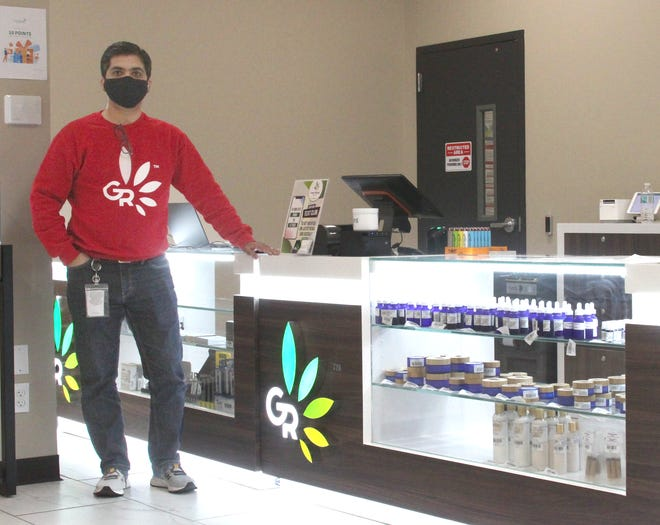Jay Patel, owner of Green Releaf in Moberly, stands next to a display of medical marijuana products for state-approved patients.