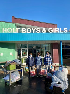 Rohan Chitre (right) and friends Charlie Romeis (left) and Sam Gotham drop off much-needed coats and food Wednesday at the Boys and Girls Club of Rochester.
