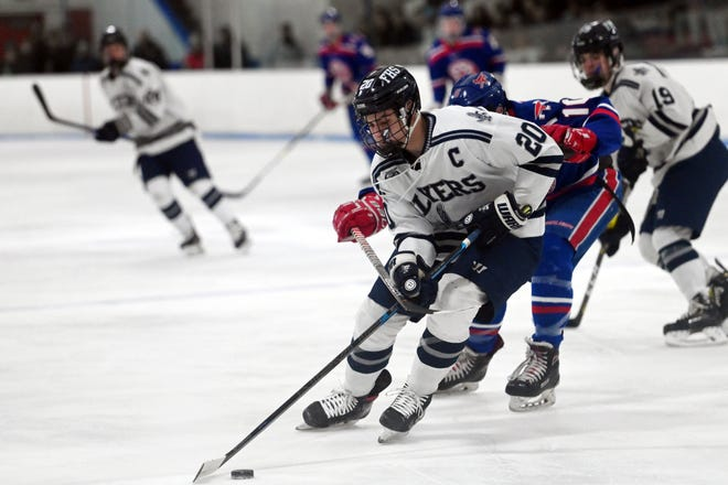 Framingham High captain Jared Shimelman takes the puck up the ice during the championship game of the Ed Cahoon Hockey Tournament against Burlington at the Burlington Ice Palace in February 2020. The Flyers have played in the Super 8 hockey tournament in each of the last two years that it was held.