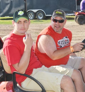 Peyton Rigsby and his father, Darcy, chat with racing personnel at Fairbury Speedway.