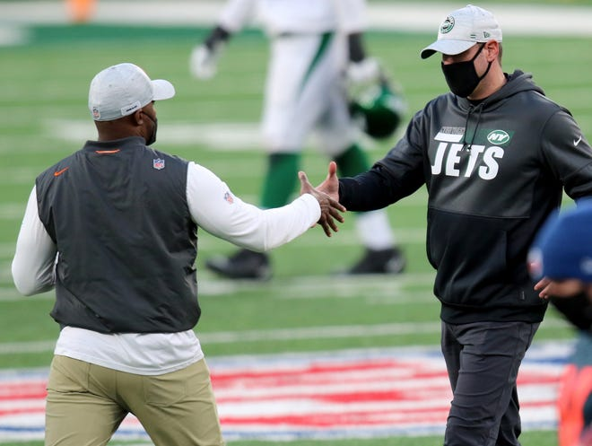Dolphins coach Brian Flores (left) and Jets coach Adam Gase shake hands after last Sunday's Miami win at MetLife Stadium.