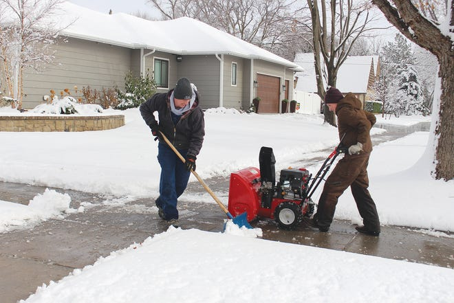 Terry Williamson (on the shovel) and Josh Williamson (snow machine) team up to clean off the sidewalks at the corner of Sixth and Oak streets Wednesday in Pratt.