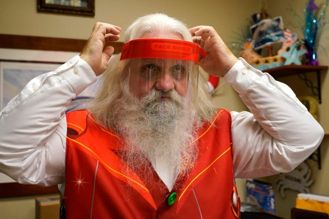 Brad Six adjusts his protective face shield as he prepares to work as Santa Claus at Bass Pro Shops in Miami.