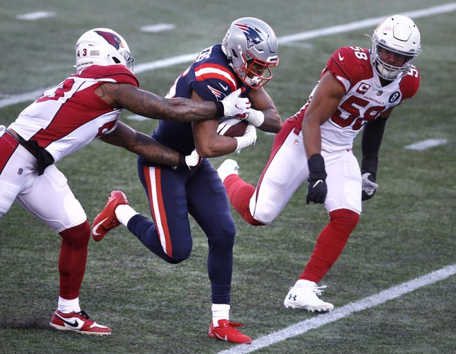 New England Patriots wide receiver Jakobi Meyers tucks the ball after making a catch in front of Arizona Cardinals defenders Haason Reddick and Jordan Hicks during the first half of their game on Sunday, Nov. 29, 2020, in Foxboro.