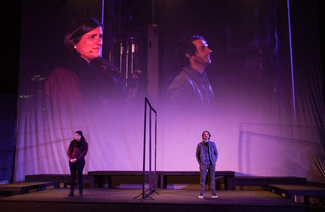 """Rachel Dulude, as quantum cosmologist Marianne, and Josh Short, as beekeeper Roland in """"Constellations,"""" a drive-in play jointly produced by Wilbury Theatre Group and WaterFire Providence. Behind them is the big screen that projects their performances to the audience, watching from their cars."""