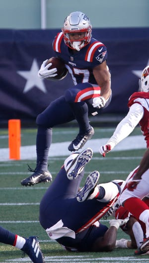 Patriots running back Damien Harris vaults over would-be tacklers as he heads downfield during a game against the Arizona Cardinals last November.