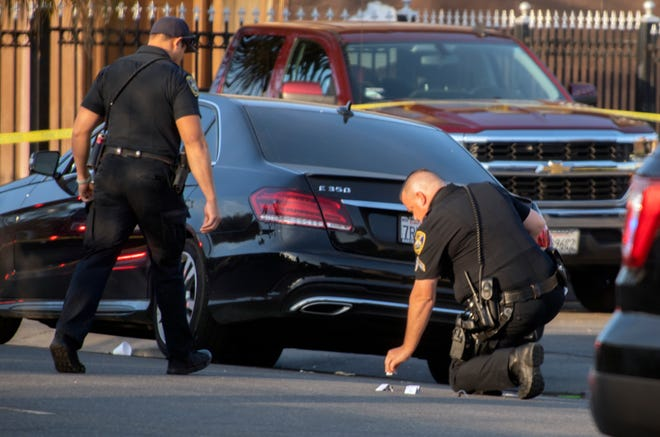 A Stockton police officer lays down markers to label evidence at the scene of a shooting at Manchester Avenue and El Monte Street Wednesday in Stockton.