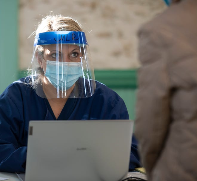 Michelle Restaino checks in a person to be tested at a recent COVID testing clinic at Freedom Town Hall.