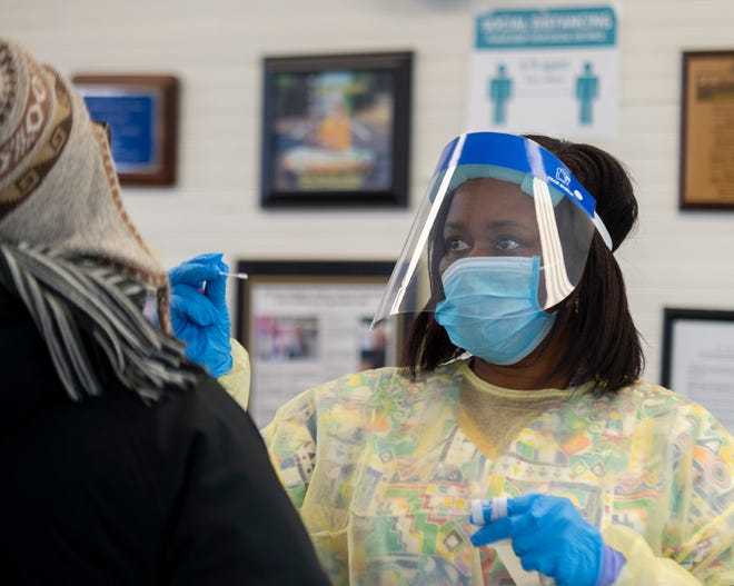 Carmella Pope administers a test at a free free walk-in COVID testing clinic at Freedom Town Hall. The clinic was hosted by the Portage County Health District, and Visit Healthcare is the third party organization registering people and administering the tests.