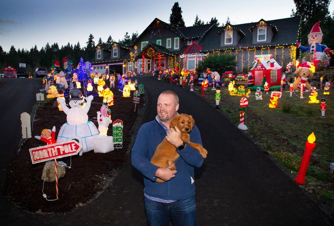 Ryan Hoffstot, with dog Sadie Mae, watches for visitors to his family's large Christmas light display on Camas Swale Road west of Creswell.