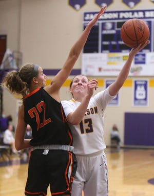 Emma Dretke (13) of Jackson puts up a shot while being guarded by Hoover's Angela Roshak (22) during their game on Dec. 2 at Jackson