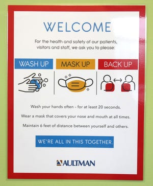Health protocols are displayed on signage at the newly opened AultmanNow Urgent Care in Louisville on Thursday. Stark County moved to Level 4 or purple on the state's health advisory system Thursday.