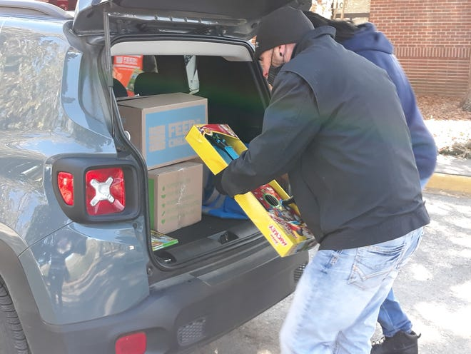 Volunteers load food, personal products and toys into cars at Bloomingdale Elementary on Wednesday.