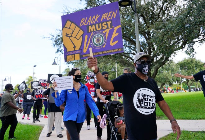 Supporters of restoring Florida felons' voting rights march to an early voting precinct prior to the Nov. 3 election. [AP Photo/Marta Lavandier]