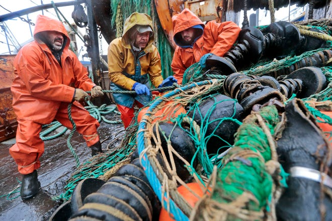 Under driving rain, fishermen aboard the New Bedford fishing boat Sao Paulo, (l to r) Tony Borges (owner/captain), Joao Gomes, and Joshua Azul change the nets from groundfish, to fluke netting.
