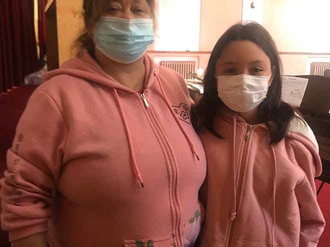 Santa Fuentes and her granddaughter, Emiliana Alvarez, 9, stand in the chapel at the Salvation Army in New Bedford.