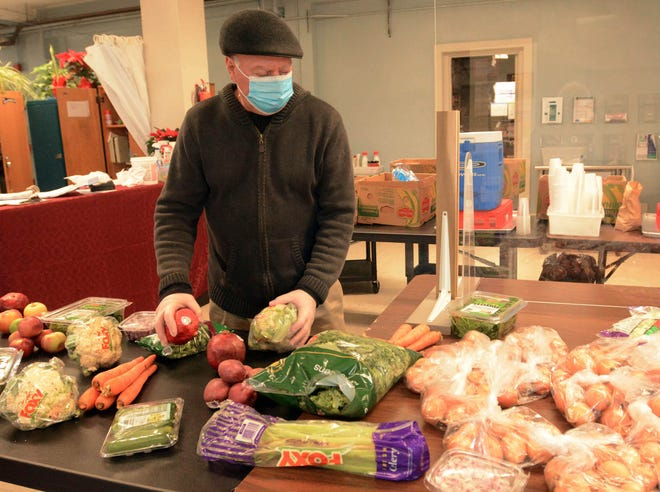 Volunteer Robert Groner of Norwich sets out vegetables for lunch Thursday for the next person at the St. Vincent de Paul Place soup kitchen in Norwich. [John Shishmanian/ NorwichBulletin.com]