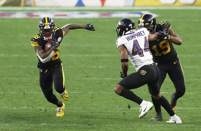 Steelers wide receiver Diontae Johnson, left, runs after a catch as wide receiver JuJu Smith-Schuster, right, blocks Ravens cornerback Marlon Humphrey (44)  during the second quarter Wednesday at Heinz Field.