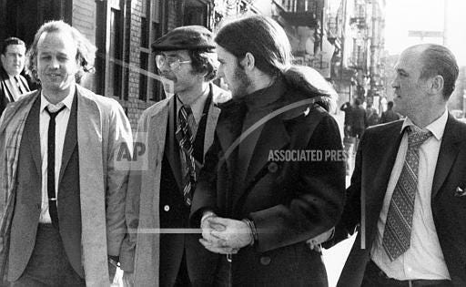 Three men described by police as members of the Weathermen radical group are escorted from a police station in lower Manhattan by a detective, right, Dec. 4, 1970. They were arrested outside an East Side bank which detectives said they were getting ready to firebomb. From left to right: Richard Palmer, Martin Lewis, and Christopher Trenkel. Detective is unidentified.
