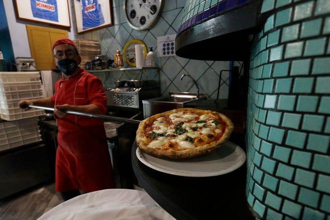 A masked Eugenio Iorio bakes a pizza at a restaurant in Naples, Italy, Nov. 14.