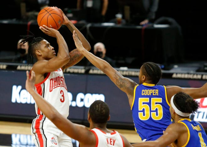 Ohio State's Eugene Brown shoots over Morehead State's Ta'lon Cooper during the first half in Columbus, Ohio.
