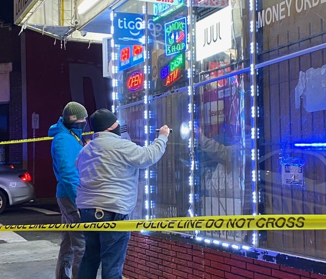Police look at bullet holes in the window of the Rock & Smoke Shop at 830 Main St., Wednesday night in Worcester after a shooting.