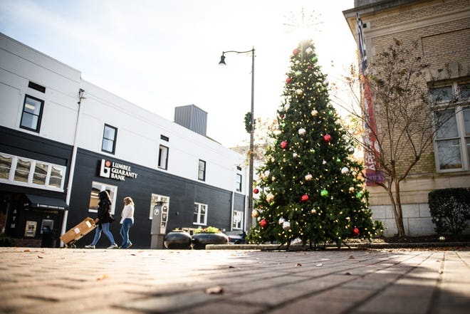 A community Christmas tree stands in front of the Arts Council building on Hay Street in downtown Fayetteville on Thursday, Dec. 3, 2020. In the background is Lumbee Guaranty Bank, which opened in February. The COVID-19 pandemic first reached crisis in the state and in the U.S. the following month. Fayetteville and other NC cities and towns face a long economic recovery, with the rest of the nation.