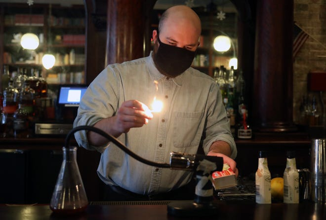 Bartender Tyler Sole prepares to light a smoker to put the finishing touches on a drink called the Uptown Old Fashioned, a choice of bourbon or rye with vanilla syrup and angostura bitters and smoked with cinnamon bark, at Asterisk Supper Club, 14 N. State St. in Westerville, on Nov. 30.