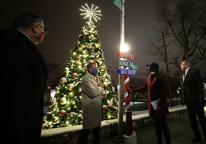 Chris Rodriquez (left), Whitehall City Council's Ward 1 representative, Tom Potter, council president, and Wes Kantor, at-large council member, right, watch as Mayor Kim Maggard flips the switch to the bring on the lights during Whitehall's virtual Christmas tree-lighting ceremony Dec. 1.