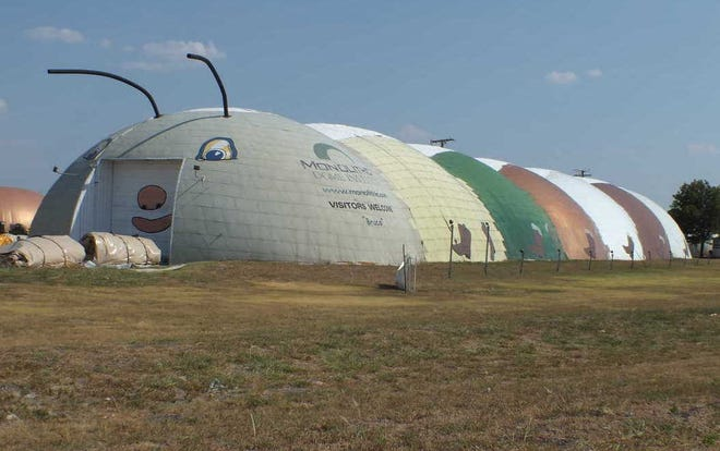 """Monolithic Constructors Inc.'s iconic caterpillar, named """"Bruco,"""" attracts attention alongside Interstate 35E in Italy. The structure houses the company's production of airforms used to build domes when inflated."""
