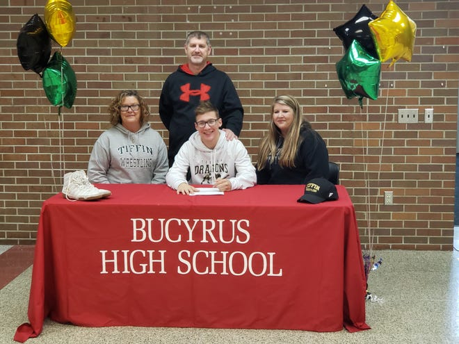 Bucyrus' Tanner Alsept signs his letter of intent to continue his wrestling career at Tiffin University. His mother Lisa, left, sister Jessica Swerlein, right, and coach Spencer King surround him.