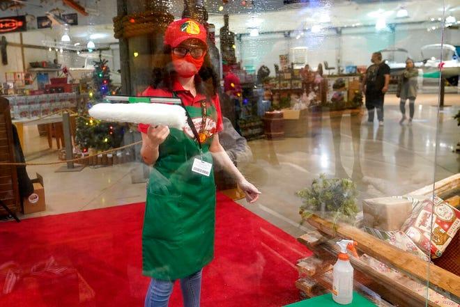 Monica Lopez membersihkan penghalang transparan yang melindungi Sinterklas dan pengunjung.