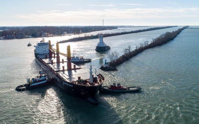Kapal tunda membantu kapal barang Harvest Spirit, mendarat di tempat yang dikenal sebagai Hole-in-the-Wall di Livingstone Channel di Sungai Detroit antara Grosse Ile, Mich., Dan Pulau Bob-Lo, Kanada, Kamis, 3 Desember, 2020.