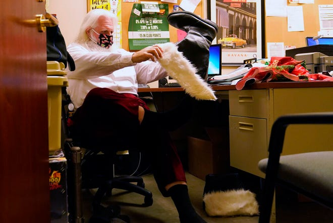 Brad Six mengenakan masker pelindung wajah saat mengenakan sepatu botnya bersiap untuk bekerja sebagai Sinterklas di Bass Pro Shops, Jumat, 20 November 2020, di Miami.