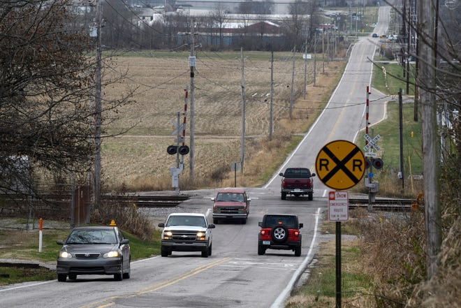 Vehicles drive over a railroad crossing along West Mill Road near the intersection of Kratzville Road in Evansville, Ind., Thursday afternoon, Dec. 3, 2020.