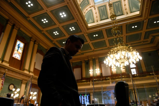 Republican Rep. Dave Williams hangs his head as he walks the sidelines of the House floor, while opting not to wear a face mask during a special legislative session at the Colorado State Capitol on Wednesday, Dec. 2, 2020, Denver. Colorado lawmakers have passed several bills offering assistance to restaurants and food pantries struggling to keep their doors open during the coronavirus pandemic. The special session that was called by Gov. Jared Polis ended on Wednesday.