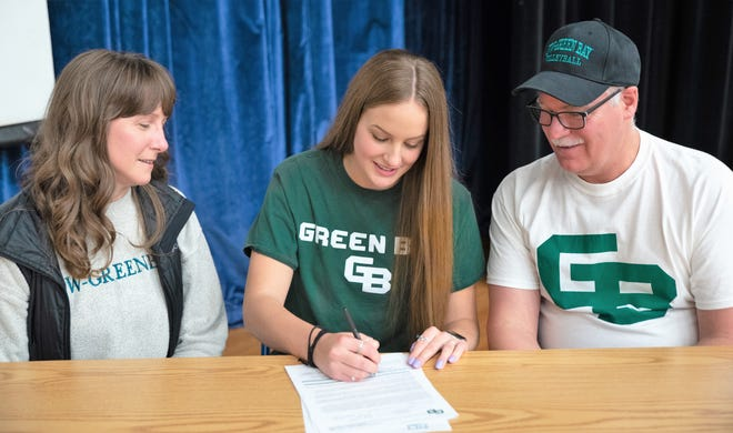 Cora Behnke signs to play volleyball with UW-Green Bay on Nov. 12 at Oconto High School, as her parents Tracy and Steve look on.