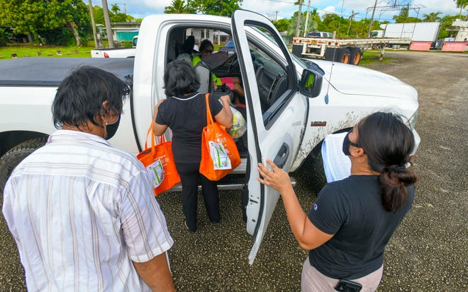 Talofofo Mayor's Office employees place food commodity bags into a resident's vehicle during a drive-through distribution at the mayor's office on this Dec. 3 file photo.