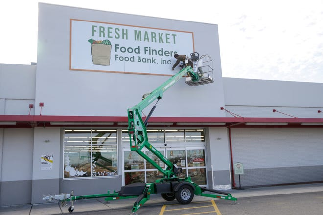 Workers install a sign for the Food Finders Food Bank Fresh Market, 2200 Elmwood Ave., Thursday, Dec. 3, 2020 in Lafayette.