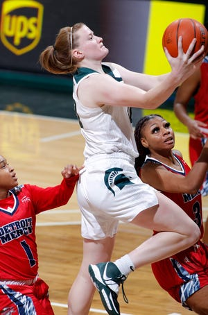 Michigan State's Julia Ayrault goes up for a layup against Detroit's Sammiyah Hoskin, right, and Alicia Norman, left, Wednesday, Dec. 2, 2020, in East Lansing, Mich. Michigan State won 82-45.