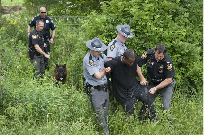 Ashland County Sheriff's Office then Capt. Carl Richert helps Ohio Highway Patrol troopers bring a limping fugitive through the Interstate 71 perimeter fence after he fled from the patrol and was in a creek just south of U.S. 250 interchange. He was captured by Ruger, deputy Mike Freelon's K9, in this News Journal 2004 file photo. Dave Polcyn/News Journal
