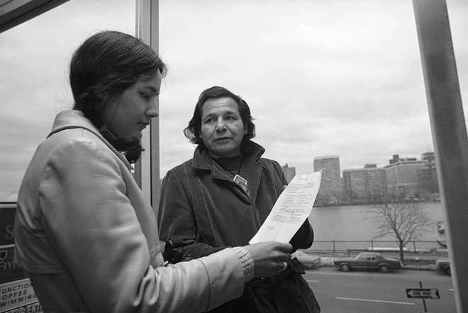 Eddie Benton, right, a holy man of the Chippewa Indian Tribe, shows a prayer he wrote to Linda Jeffers of Vineyard Haven, Martha's Vineyard, Mass., a member of the Wampanoag Tribe, on Nov. 4, 1971, in Cambridge, Mass. Eddie Benton-Banai, one of the founders of the American Indian Movement that was formed partly in response to alleged police brutality against Indigenous people, has died. He was 89. A family friend says Benton-Banai died Nov. 30, 2020, at a care center in Hayward, Wis., where he had been staying for months.