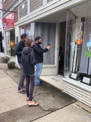 Passersby enjoy the miniature fiddles in the drug store window.