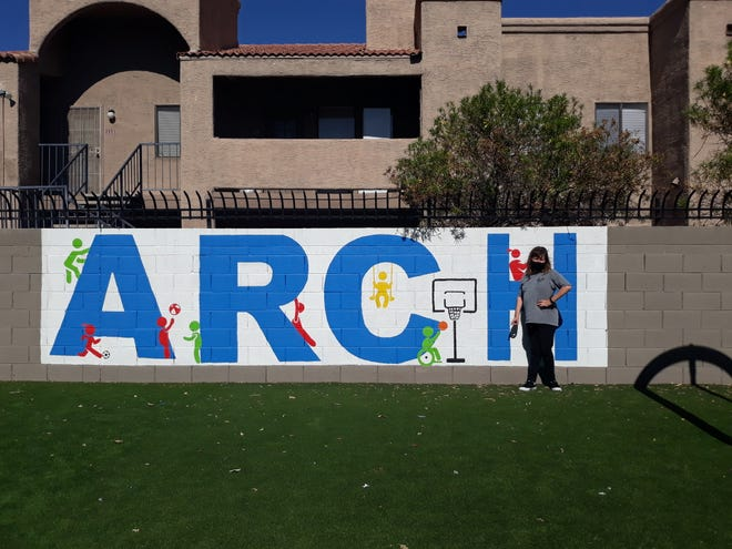 Caitlin Mehle, a student in the ARCHKids program, stands by the ARCH sign at the recreational center in Phoenix.