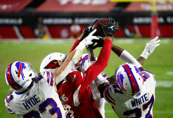 Cardinals' DeAndre Hopkins (10) catches a game-winning touchdown catch over Bill's Tre'Davious White (27) and Micah Hyde (23) with 2 seconds left in the fourth quarter at State Farm Stadium in Glendale on Nov. 15, 2020.